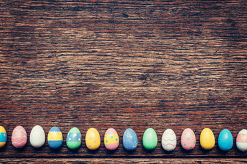 Colorful easter egg on wood background with space. Vintage toned