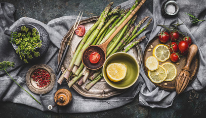 Various asparagus ingredients on rustic kitchen table background with bowls and tools, top view. Dark style