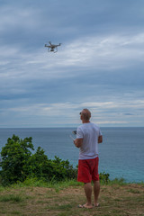 Man attentively watching drone while standing with remote controller of drone in sunny summer day over sea and sky background