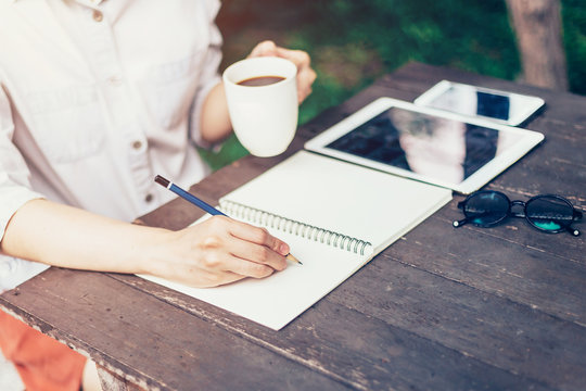 Hand woman writing notebook and holding cup coffee on wood table