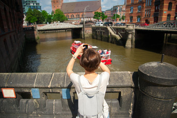 Girl making photo of city using smart phone