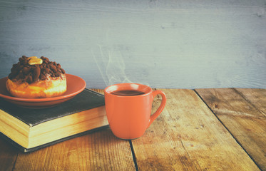 donut next to cup of coffee and the book