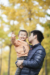Happy real father and son kissing in front of ginkgo trees