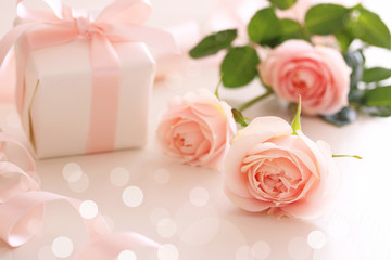 Beautiful pastel pink roses with gift on the table