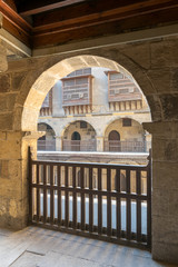 Angled view of one arch with interleaved wooden balustrades at the arcade surrounding the courtyard of caravansary (Wikala) of Bazaraa, Medieval Cairo, Egypt