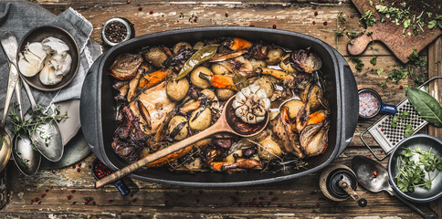 Country stew in vintage casserole with cooking spoon and roasted vegetables on rustic kitchen table...