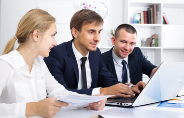 Positive business male sitting with coworkers