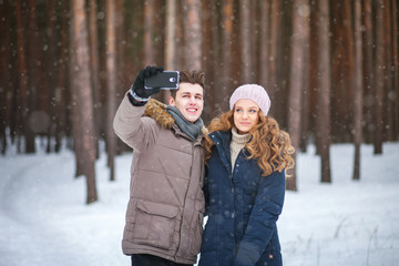 people,season,love,technology and leisure concept  - happy couple taking picture with smartphone selfie stick on over winter background