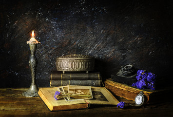 Classic still life with vintage books placed with old camera,illuminated candle,silver box,dry flowers and old pictures on rustic wooden background..