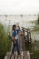Traveler asian woman posing and standing on the wooden bridge an