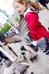 child with pigeon in Dam Square in Amsterdam in the Netherlands