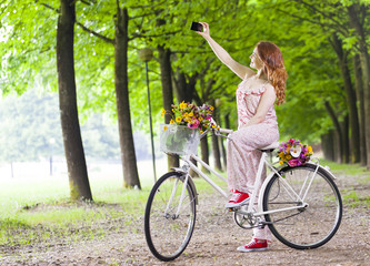 Beautiful girl on vintage bike taking a selfie at the park