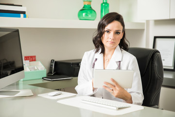 Hispanic female doctor using a tablet