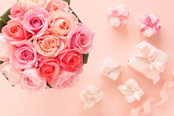 Bouquet of beautiful pink roses with gifts on pastel  pink background