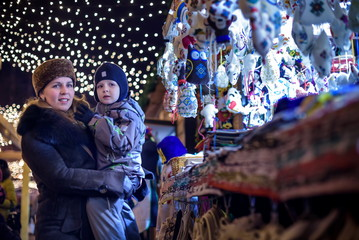 Happy family spend time at a Christmas street market fair in the