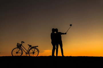 Silhouette of sweet couple in love happy time and bicycle in bea