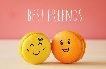 Image of two cute macaroons with drawn smiley faces