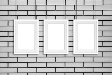 Three frames hanging on cords against bricks wall, gallery style decor mock up