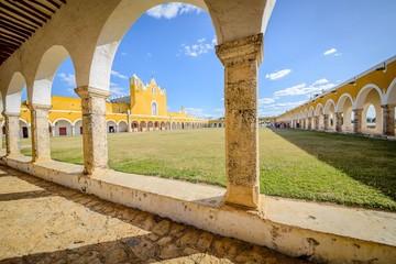 Fototapeta Izamal Meksyk żółty kościół widok spod obejścia z podcieni kolumny łuki plac przed kościołem obraz