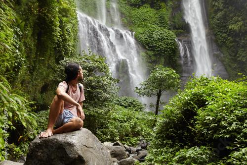 293707d41bb Young stylish backpacker enjoying mountain trip alone. Caucasian man  trekking in rainforest