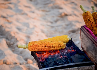 Corn grill on the stove with fire and charcoal
