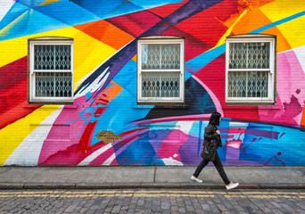 shuttered windows in wall covered in rainbow street art Wall mural