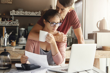 Unhappy Caucasian family having economic trouble, not able to pay out debts. Supportive young man trying to cheer up his worried wife in glasses who is feeling stressed, facing financial problem