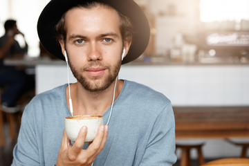 People and leisure concept. Headshot of attractive young hipster in trendy black hat drinking coffee and listening to audiobook online on earphones while relaxing at cafe against blurred background