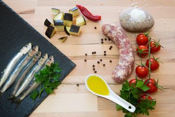 Salsiccia e sardine  cruda con varie spezzi e ortaggi su tavolo di legno