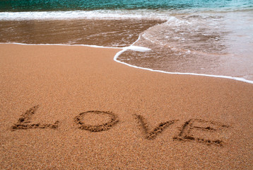 """written words """" love """" on sand of beach with wave on background"""