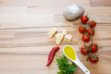 Pomodoro e formaggio grana con sale e peperoncino per una buona preparazione su tavolo di legno