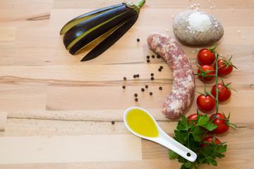 Salsiccia e melanzana cruda con varie spezzi e ortaggi su tavolo di legno