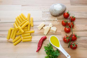 Pasta cruda con varie spezzi e ortaggi su tavolo di legno