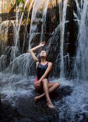 Teen girl relaxed under handmade waterfall