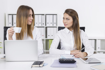 Two young women looking at each other in office