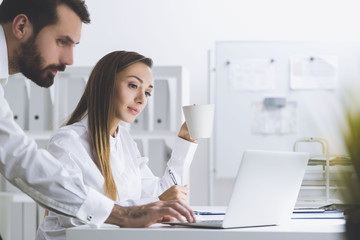 Bearded man and a woman in an office, side view