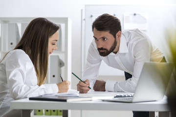 Man is looking at his colleague and writing