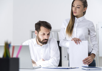 Man typing, woman talking to him