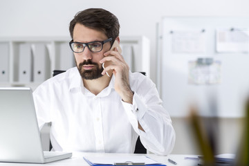 Bearded businessman in glasses on the phone