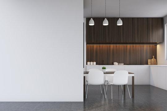 Kitchen with dark wood furniture, blank wall