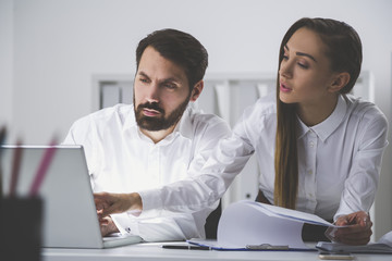Bearded man and businesswoman in office