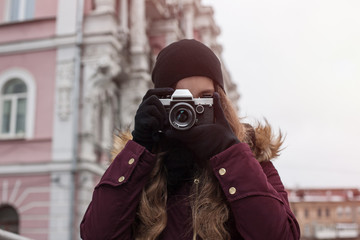 Hipster girl tourist with retro camera taking photos on city str