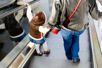 Back view of mother and child together on escalator background. Shopping mall, airport travel, love care