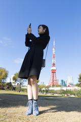 若い女性 スマホ 自撮り 写メ 東京タワー背景 快晴 青空