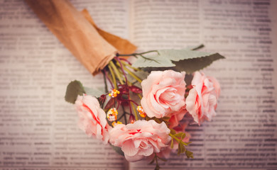 Artificial roses place on unfocused book- select focus and pink