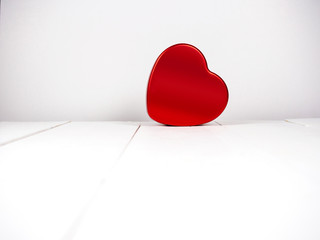 Red heart shape on white wooden background