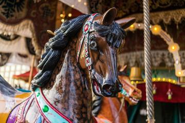 Carousel at a carnival or festival. Decorative ornate horse at a fun fair.
