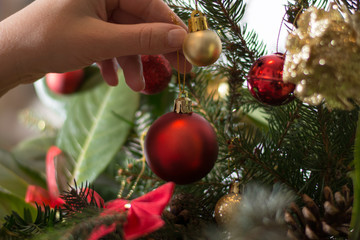 Decorating Christmass bouqet  with red ornaments and tree branch