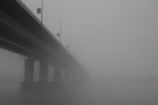The bridge over the river lost in the thick fog.