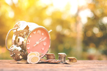 coin with alarm clock on old wood and tree bokeh background, a color of vintage tone concept time to save money